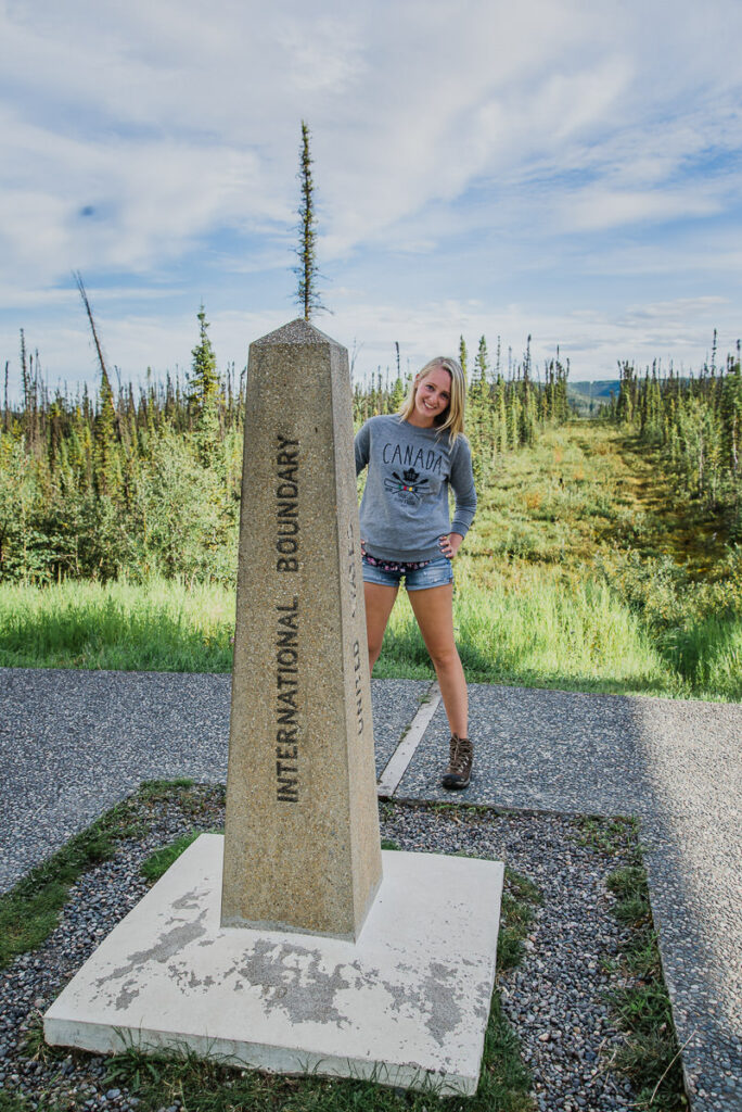 Young woman standing on the border of the Yukon and Alaska International Boundary.