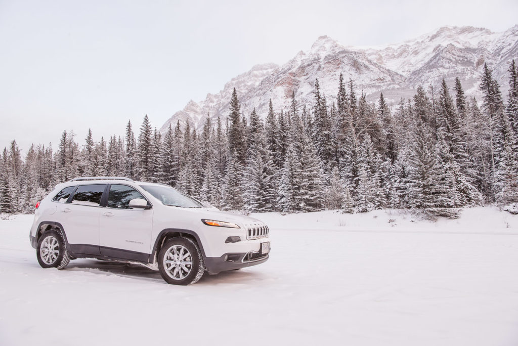 Jeep Cherokee sitting in a snowy parking lot with the Rocky Mountains in the background in December on the Icefields Parkway.