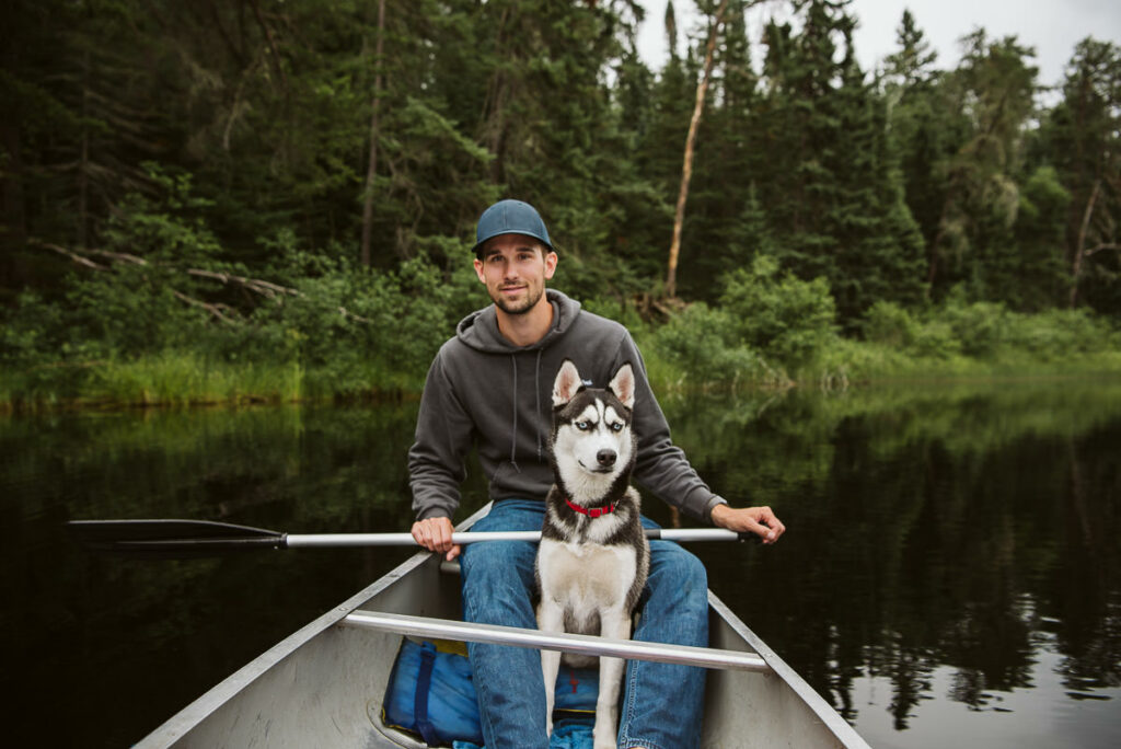 Young man and husky puppy in a canoe in Quetico Provincial Park