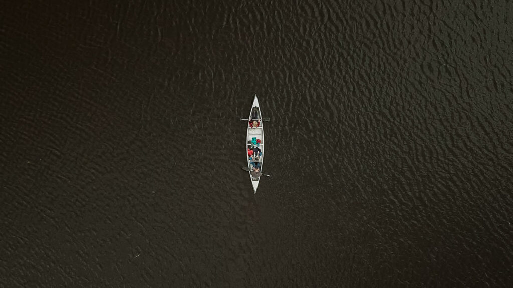 Arial photo of two young adults and their husky paddling through the interior of Quetico Provincial Park.